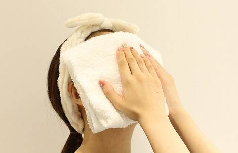 蒸しタオルを顔にあてる女性